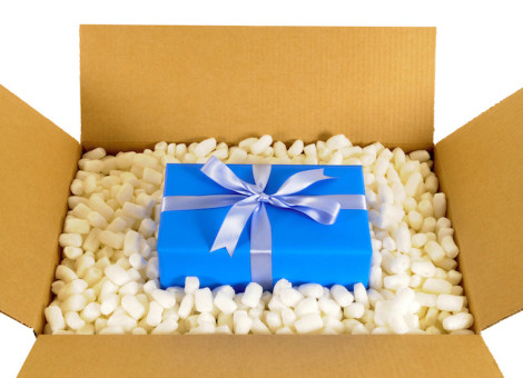 Cardboard box with blue gift and polystyrene packing pieces.